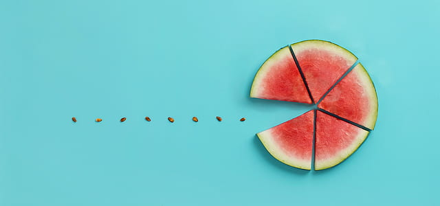 sliced watermelon Pac-Man on top of teal surface