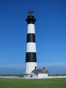 White and Black Striped Lighthouse Beside White House