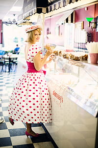 woman wearing white and pink polka-dot cap-sleeved dress front of clear glass display counter