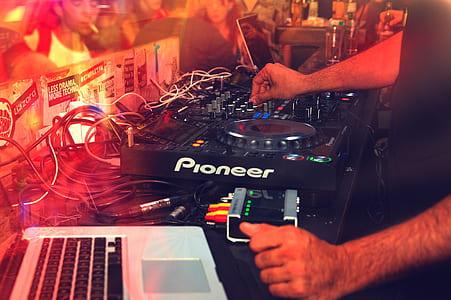 person playing black Pioneer DJ turntable beside MacBook Pro