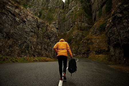 photo of person wearing yellow hoodie and black pants holding backpack walking on roadway between mountain