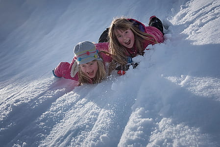two girls in pink jacket playing on snow