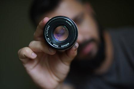 Photographer holding camera lens