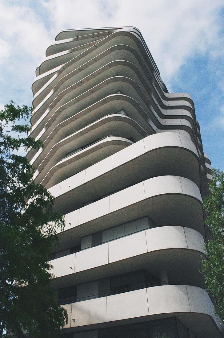 white concrete tall building near tall tree