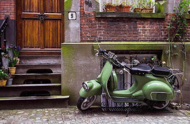 green motor scooter parked on roadside