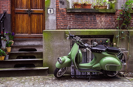 green motor scooter parked on roadside