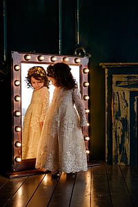 girl wearing white floral embroidered dress looking at mirror