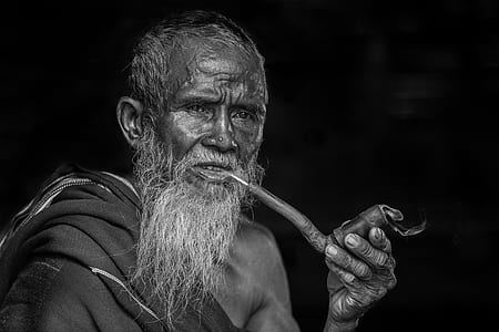man holding tobacco pipe grayscale photograph