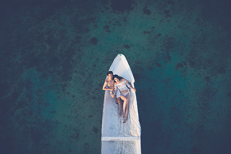 aerial photo of Couple riding white boat