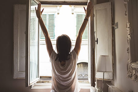 woman standing in front of opened window and putting her hands in the air