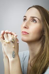 woman wearing gray top while praying