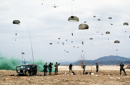 soldiers flying parachutes