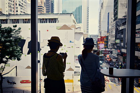 Two women looking through a window in Hong Kong, China