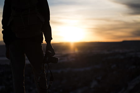 person holding camera while standing on top of the mountain during sunset