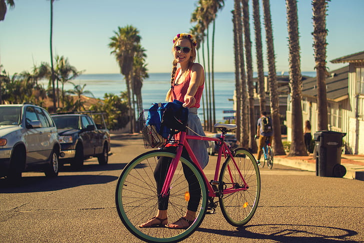 selective focus photography of woman holding pink city bike