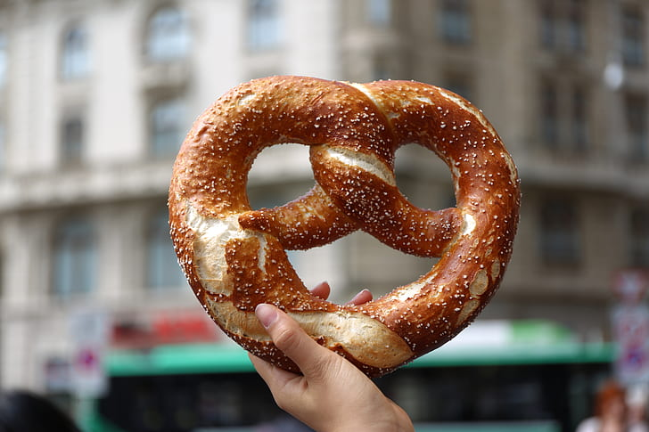 shallow focus photography of person holding pretzel