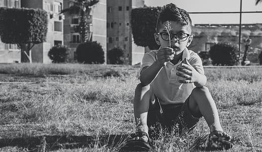 Greyscale Photo Of Boy Wearing Eyeglasses