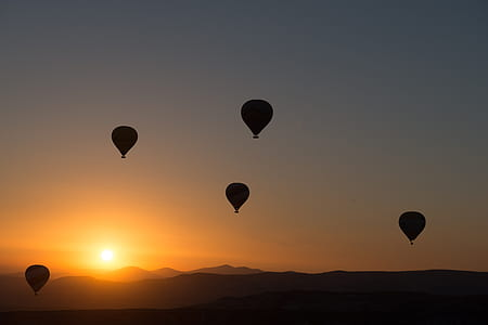 silhouette of five hot air balloons during sunset