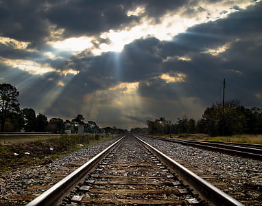photo of train rail under crepuscular rays background