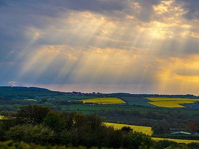 green fields under crepuscular rays
