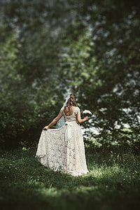 woman in white lace wedding dress holding a white bouquet surrounded with trees