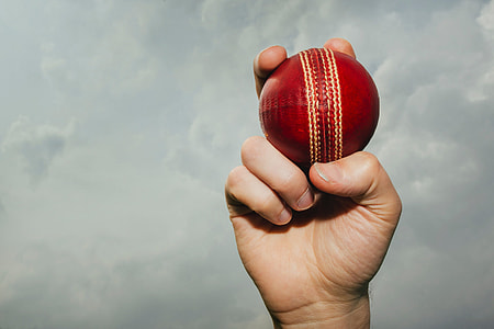 Man holding cricket ball in his hand