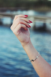 person with red manicure and silver-colored sideway cross bracelet