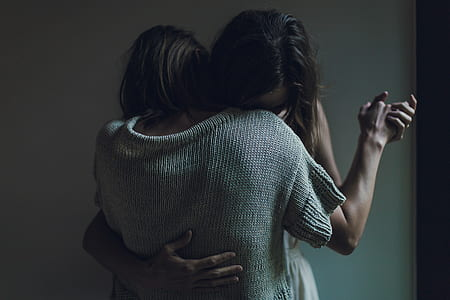 two person hugging in front of white painted wall