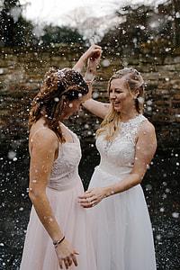 two women wearing sleeveless dress raising their hands