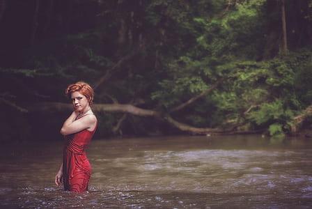 woman in body of water wearing red dress