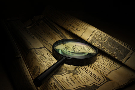 photography of magnifying glass on printed brown paper
