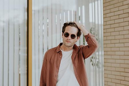 man holding his hair wearing brown button-shirt
