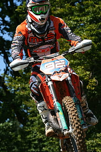 rider riding orange motocross dirt bike