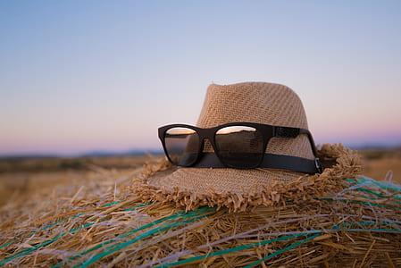 black framed wayfarer-style sunglasses on brown hat
