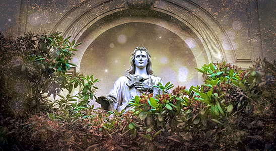 photo of gray statue surrounded by green plants