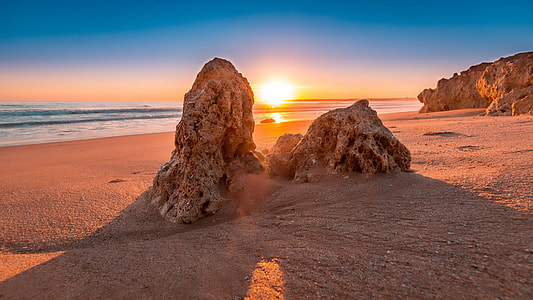 two brown rock formations near ocean during sunset