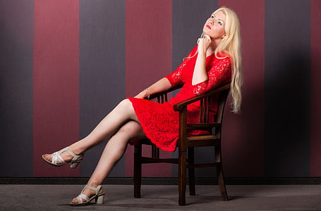 woman wearing red dress while sitting on chair