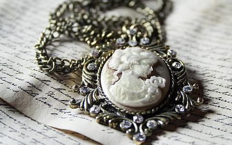 silver-colored cameo pendant