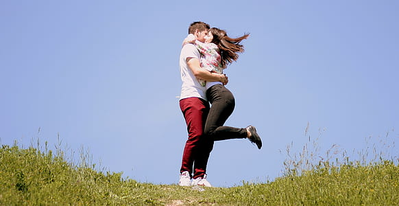 girl hugging boy with raising left foot on air surrounded by green grass in the hill under blue sky during daytime