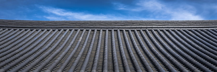 low-angle photography of roof under white clouds and blue sky