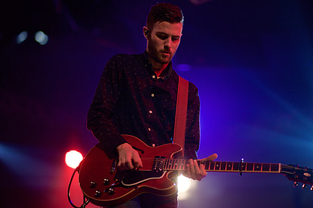 man in black dress shirt playing a guitar
