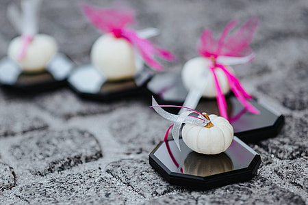 Decorative white pumpkin trinkets with ribbons on the floor