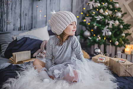 girl in gray long-sleeved shirt and knit cap sitting on white fur textile