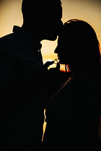silhouette of couple holding ring during golden hour