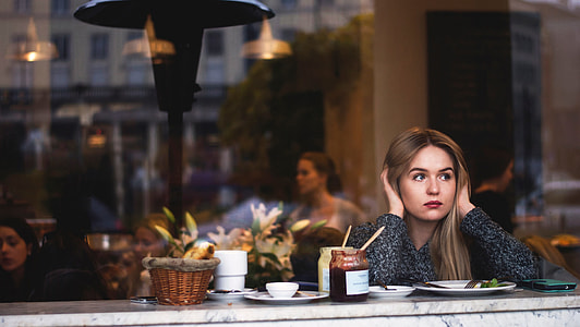 woman in grey sweater sitting in front of marble table covering her ears