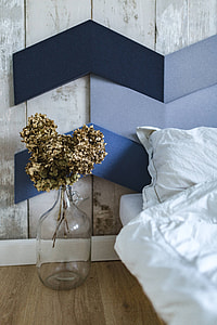 Designer bedroom with an ornamental golden plant in a jar by the bed