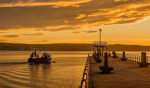 boat near dock during golden hour