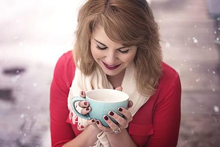 woman wearing pink shirt holding teal and white ceramic mug during winter