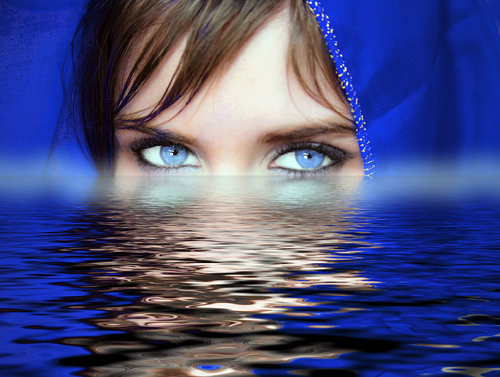 woman with blue eye lens and head scarf on body of water