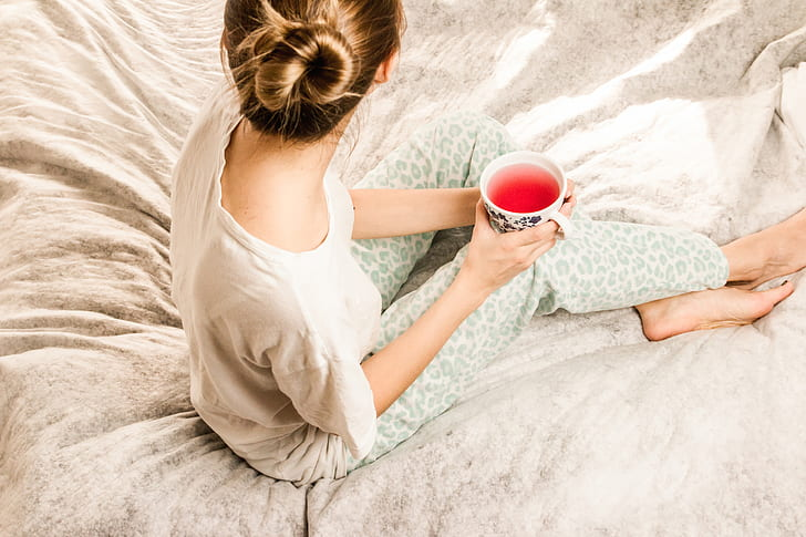 Royalty-Free photo: Woman holding white cup sitting on bed | PickPik
